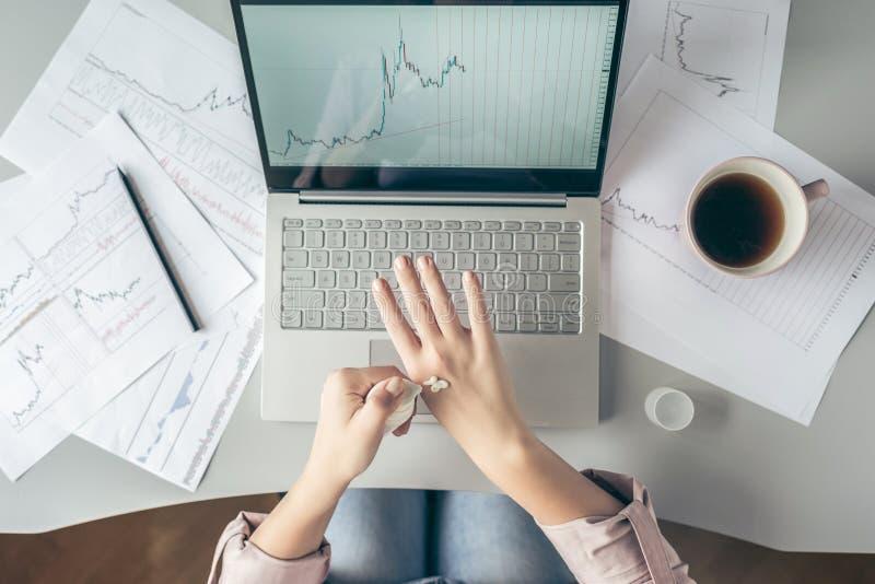 Top besk?dar affärskvinna som sitter på tabellen och applicerar handkräm som arbetar på bärbara datorn med diagram och diagram so arkivfoto