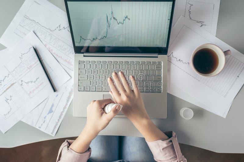 Top besk?dar affärskvinna som sitter på tabellen och applicerar handkräm som arbetar på bärbara datorn med diagram och diagram so fotografering för bildbyråer