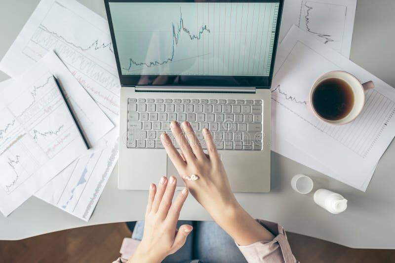 Top besk?dar affärskvinna som sitter på tabellen och applicerar handkräm som arbetar på bärbara datorn med diagram och diagram so royaltyfri foto