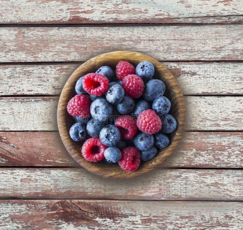 Top besk?dar Blåa och röda bär i bunke Mogna hallon och blåbär på en träbakgrund Bakgrund av blandningb?r med royaltyfri bild