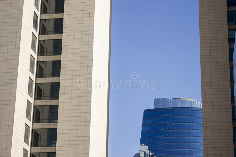 Top of a blue modern corporate high-rise building with a striped design standing in the background between a pair of twin yellowis royalty free stock photo