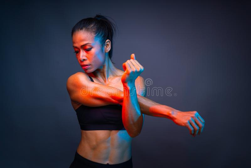 Top body part of healthy athletic asian woman with a six pack core muscle is stretching her right and left arm before fitness stock image