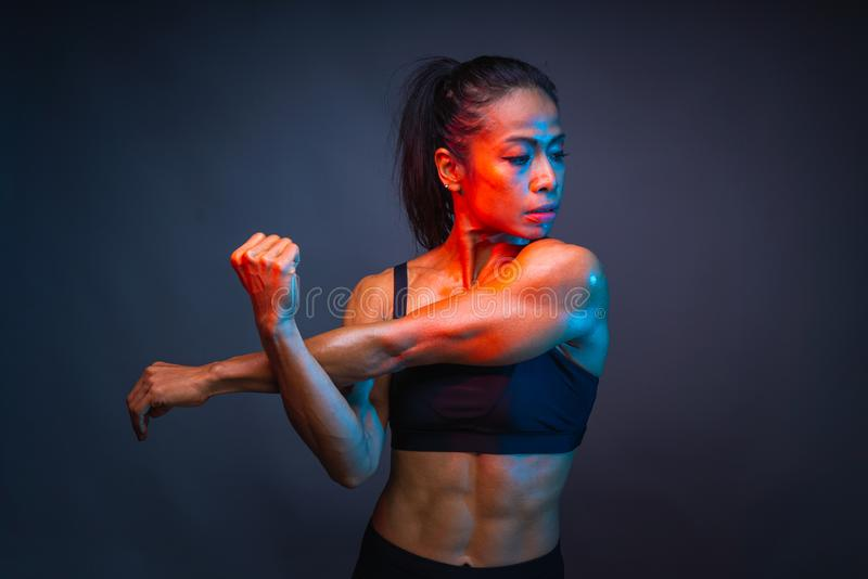 Top body part of healthy athletic asian woman with a six pack core muscle is stretching her right and left arm before fitness stock photos