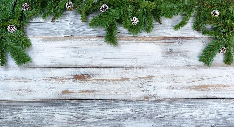 Top border of Christmas fir branches and pine cones on rustic white wooden background. Top border of Christmas tree fir branches and pine cones on rustic wood in royalty free stock photos