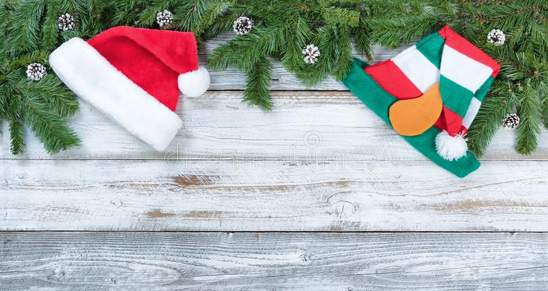 Top border of Christmas fir branches and Santa Claus hats on rustic white wooden background. Top border of Christmas tree fir branches, Santa and elf hats on stock photo