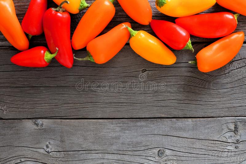 Top border of colorful mini sweet peppers over wood royalty free stock photo