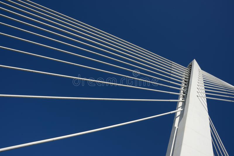 Top bridge pillar joining ropes, blue sky. Success. The different directions ropes are joining on the top of the white modern bridge pillar. The blue sky as