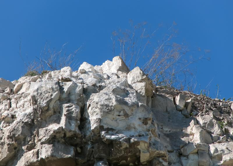 Top of chalk cliffs with rifts, cracks, stones and withered grass close-up stock photo