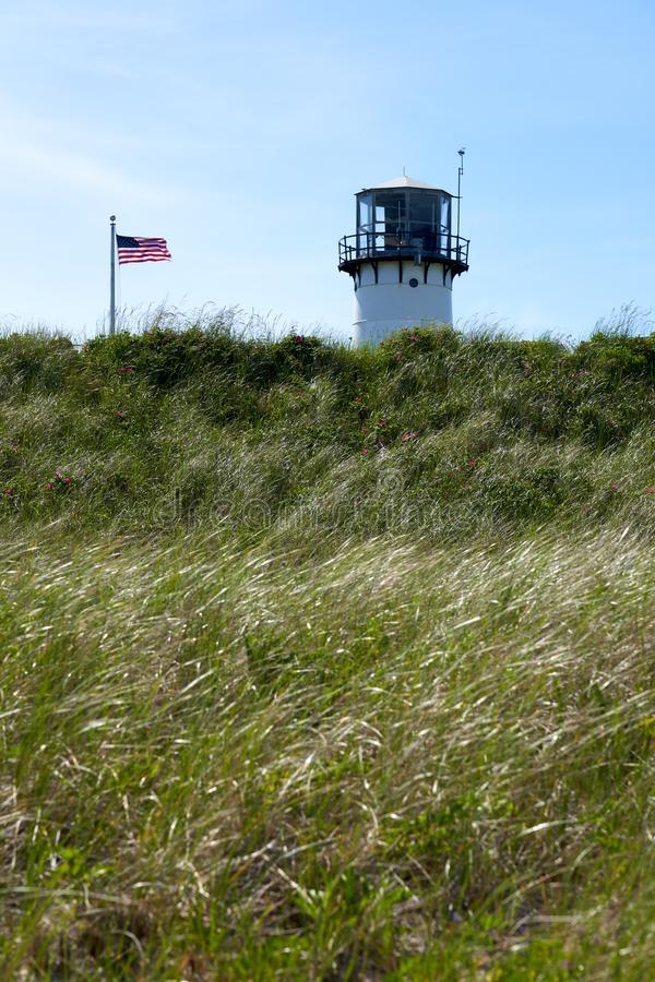 The top of Chatham Lighthouse and the United States flag. Blowing in the wind viewed from the beach looking up at the cliffs covered with grass and pink roses stock photography