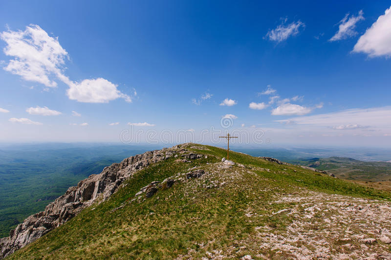 The top of Chatyr Dag. The cross on the top of the mountain. Clear weather. Narrow steppe valley on Chatyr-Dag plateau stock photo