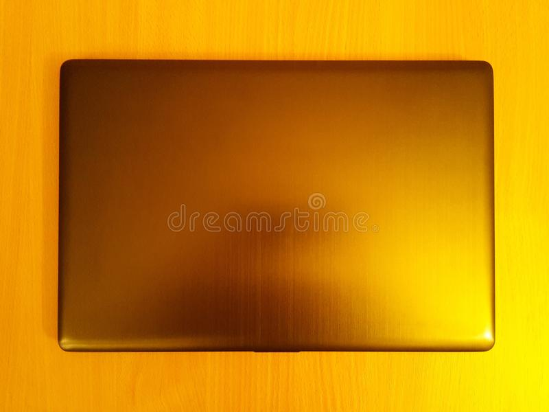 The top of a closed laptop that is laid on a wood plate royalty free stock images
