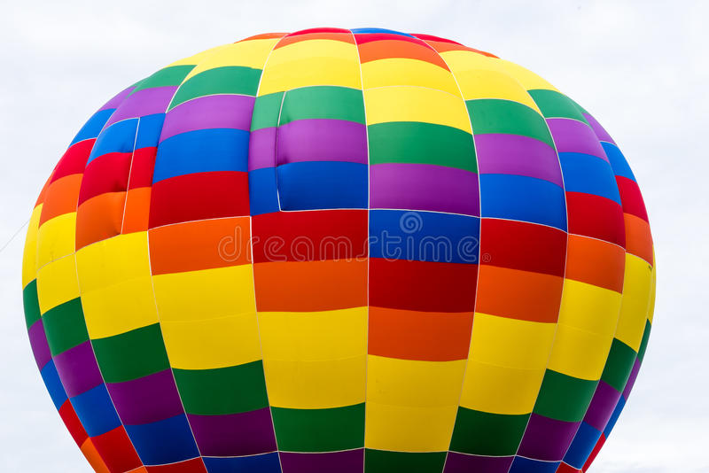 Top of a Colorful Hot Air Balloon. The top portion of a colorful hot air balloon against an almost white cloud filled sky stock photography