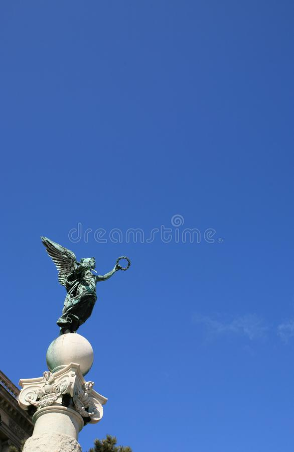 Top column statue of an angel with wings and wreath in Vienna in Austria at blue sky background. Top column statue of an angel with wings and wreath in Vienna stock images