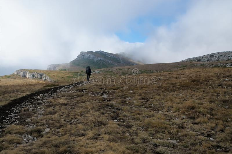A tourist at the top Crimean Chatyr-Dag mountain in autumn. The top Crimean Chatyr-Dag mountain in the central part of the mountain Crimea royalty free stock images