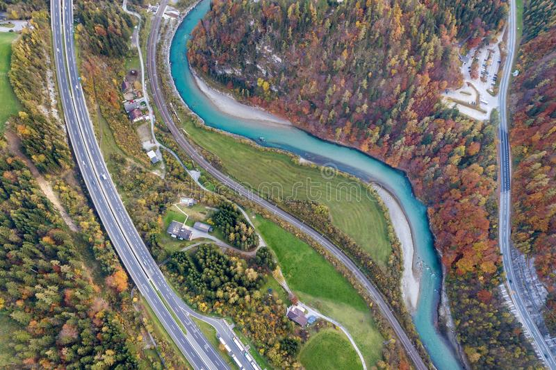Top dawn aerial view of freeway speed road between yellow autumn forest trees and blue river royalty free stock photos