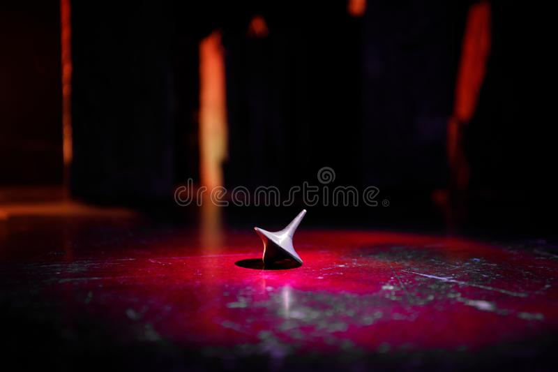 Top de giro del tótem que hace girar, tambaleándose y parando El top de giro en el espejo emerge con la luz entonada del fondo de fotografía de archivo