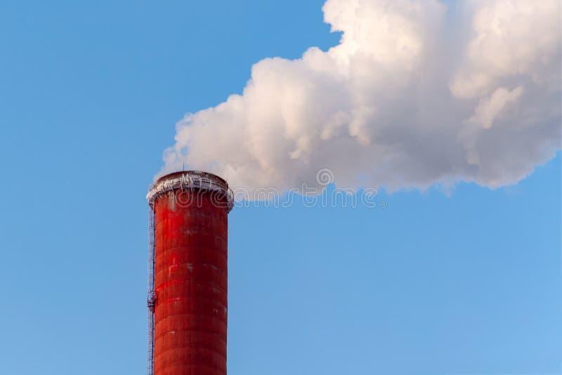 Top de la chimenea roja de una central eléctrica contra un cielo azul, cl fotos de archivo