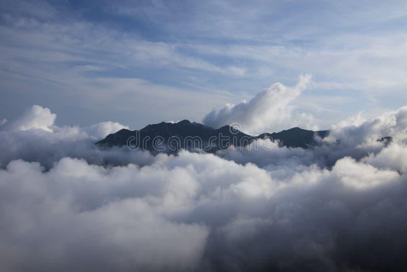 Top de la montaña sobre las nubes imágenes de archivo libres de regalías