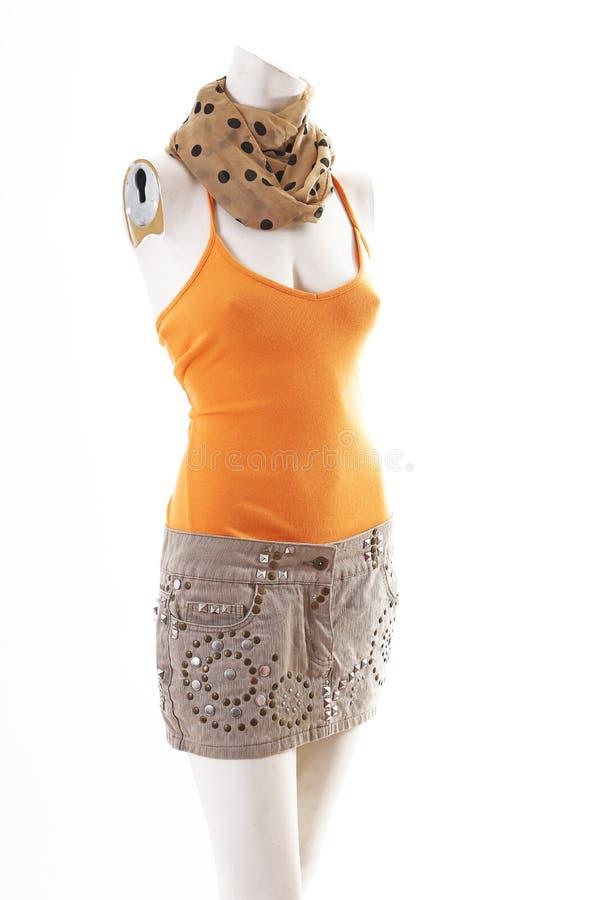 Top de la naranja y mini falda beige en la exhibición completa del body shop del maniquí Estilos de la moda de la mujer, ropa en  imagenes de archivo