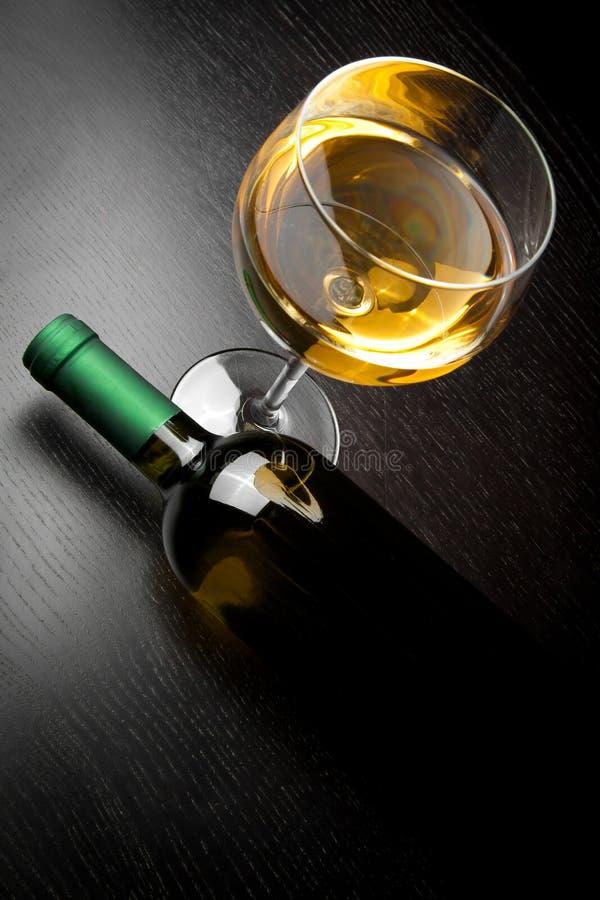Top de la vista de la copa de vino blanca cerca de la botella imagenes de archivo