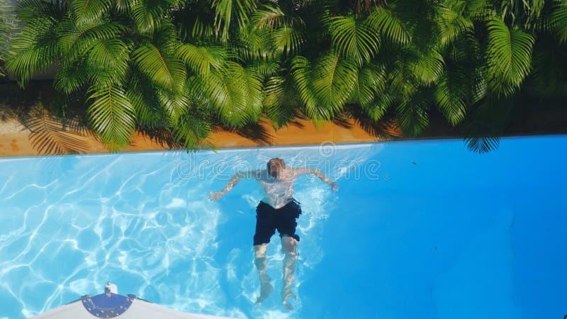 Top de la vista de la natación del hombre en piscina al aire libre fotos de archivo