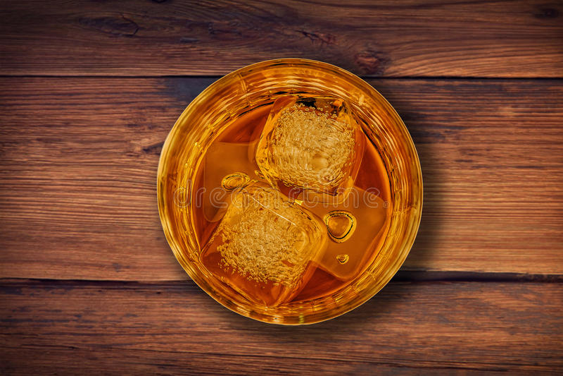 Top de la vista del whisky en vidrio con los cubos de hielo en el fondo de madera de la tabla fotografía de archivo libre de regalías