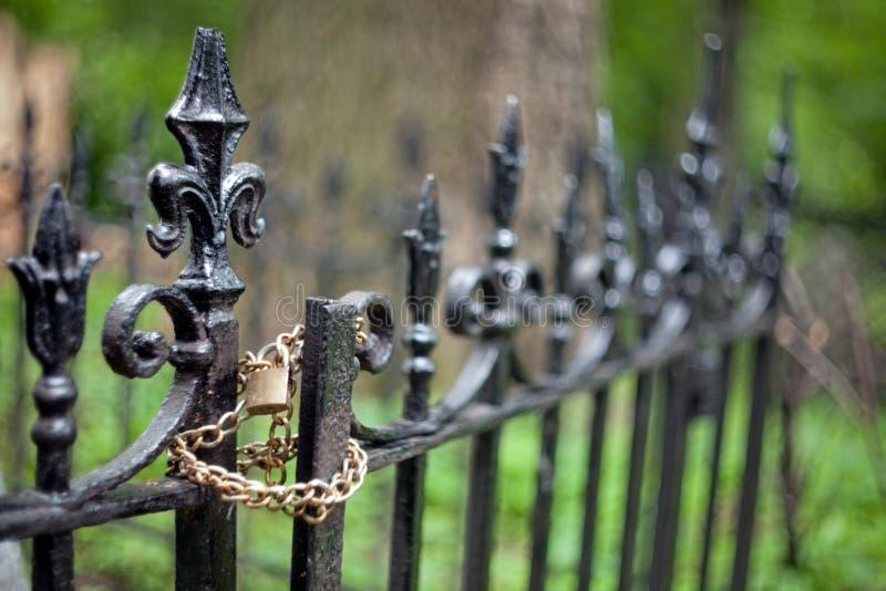 Top del metal de arte que echa en una cerca grave en la forma de un lirio del borbón con la cadena de oro y cerradura y un fondo  imagen de archivo