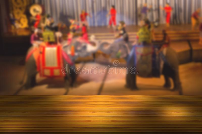 Top desk with blur fighting on an elephant show background,wooden table. Top desk with blur fighting on an elephant show background ,wooden table stock image