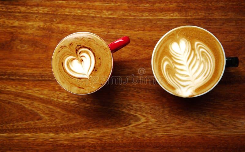 Top dos de la taza de café caliente del arte del latte en el CCB de madera de la tabla del marrón oscuro fotografía de archivo
