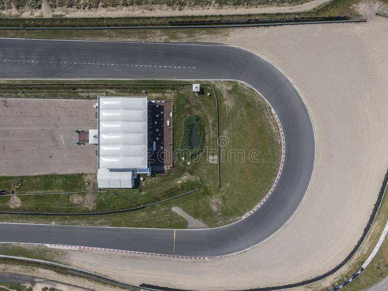 Top down aerial view of curve in motor sport race track circuit with sand roadside stock images