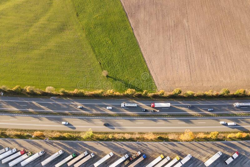 Top down aerial view of highway interstate road with fast moving traffic and parking lot with parked lorry trucks.  royalty free stock photography