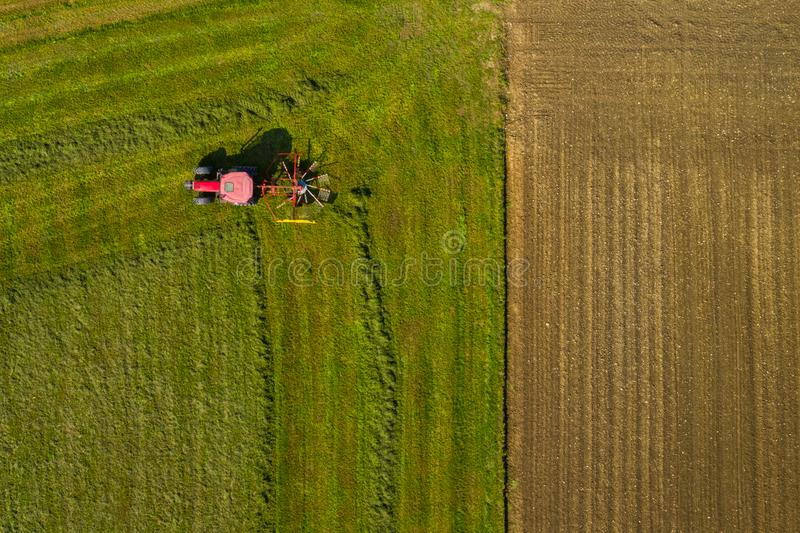 Top down aerial view of a red tractor cultivating farmland with a spinning rack. Top down aerial view of a red tractor cultivating farmland with a spinning blade royalty free stock photo