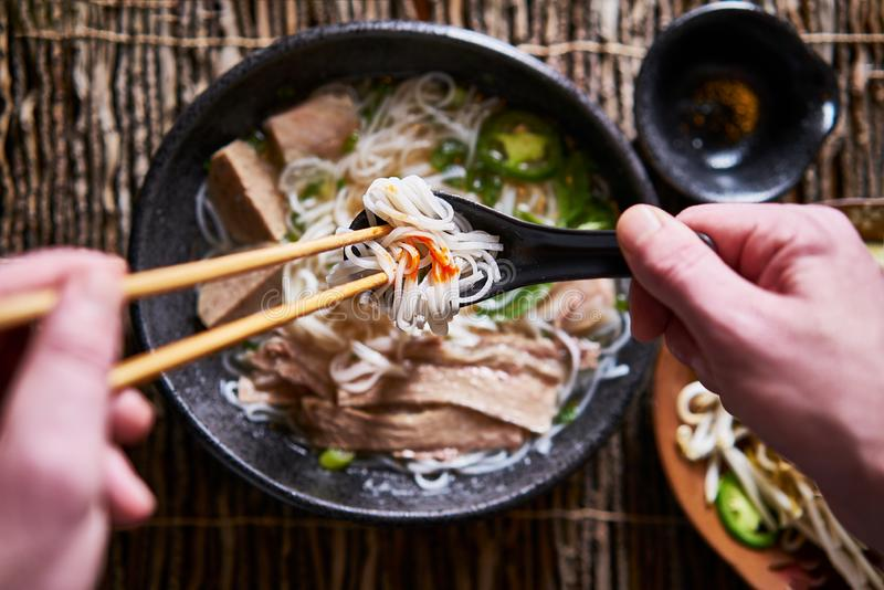 Top down composition of eating vietnamese pho with chopsticks and spoon, has dab of sriracha for flavor. Shot with selective royalty free stock images