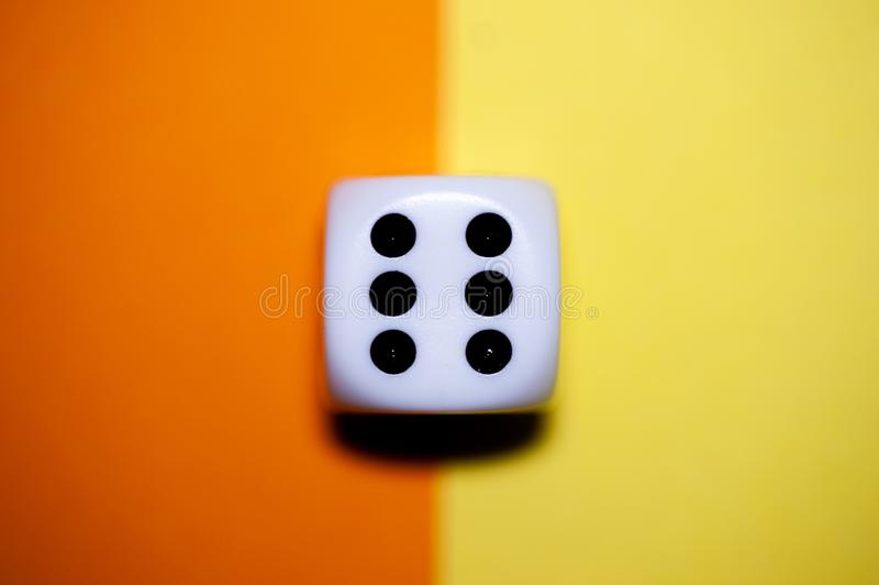 Top down die macro. Macro of a die, showing the number six. The die lays flat on a yellow and orange background royalty free stock photo
