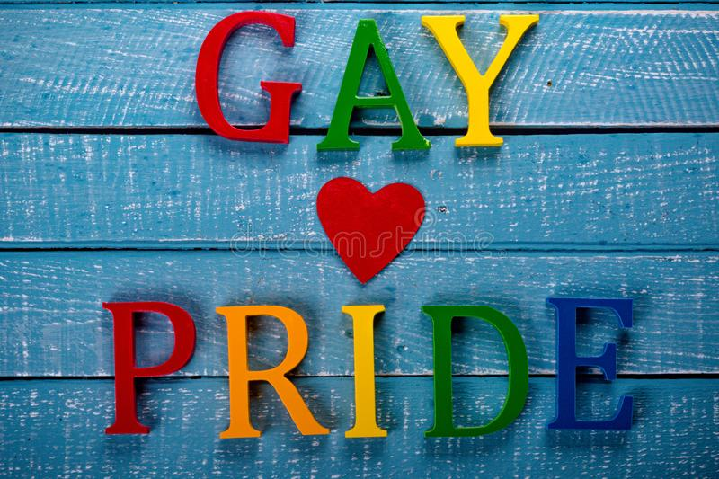 Top down photo of Gay Pride concept. Top down image showing GAY & Pride spelt in coloured letters on a blue wooden background with a red heart stock photos
