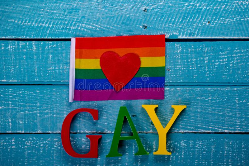 Top down photo of Gay Pride concept. Top down image showing GAY spelt in coloured letters on a blue wooden background with a pride flag and heart royalty free stock photos