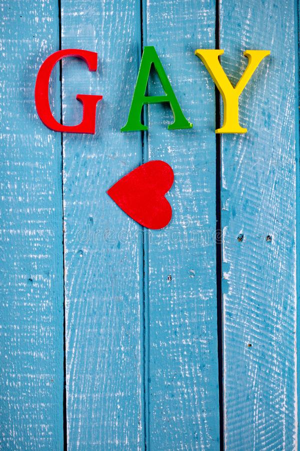 Top down photo of Gay Pride concept. Top down image showing GAY spelt in coloured letters on a blue wooden background with a red heart stock images