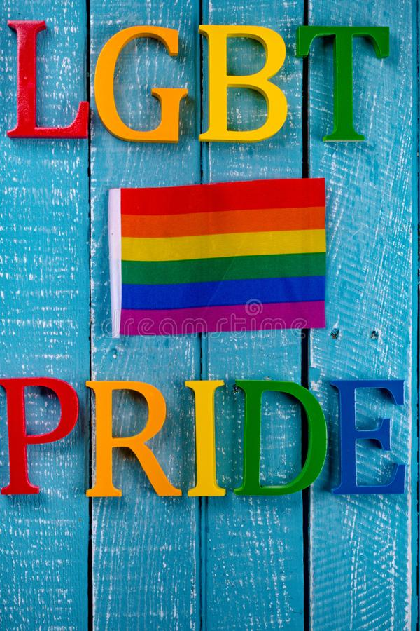 Top down photo of Gay Pride concept. Top down image showing LGBT & Pride spelt in coloured letters on a blue wooden background with a pride flag royalty free stock photography