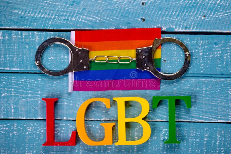 Top down photo of Gay Pride concept. Top down image showing LGBT spelt in coloured letters on a blue wooden background with a flag and handcuffs royalty free stock photo