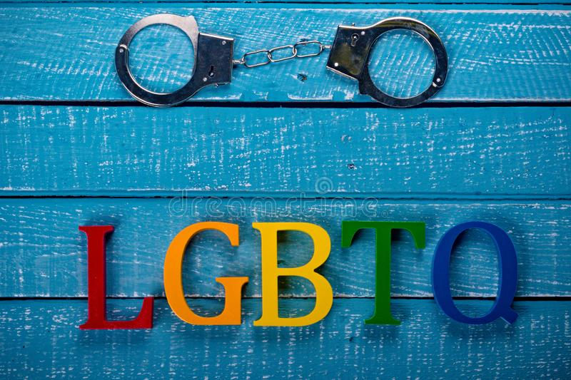Top down photo of Gay Pride concept. Top down image showing LGBTQ spelt in coloured letters on a blue wooden background with handcuffs stock images