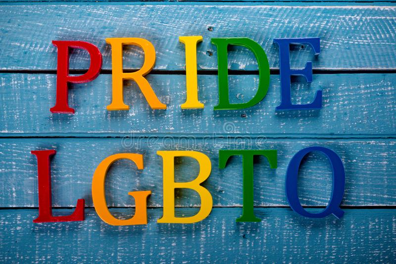 Top down photo of Gay Pride concept. Top down image showing Pride & LGBTQ spelt in coloured letters on a blue wooden background stock photos