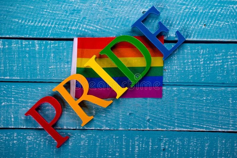 Top down photo of Gay Pride concept. Top down image showing Pride spelt in coloured letters on a blue wooden background with a flag royalty free stock image