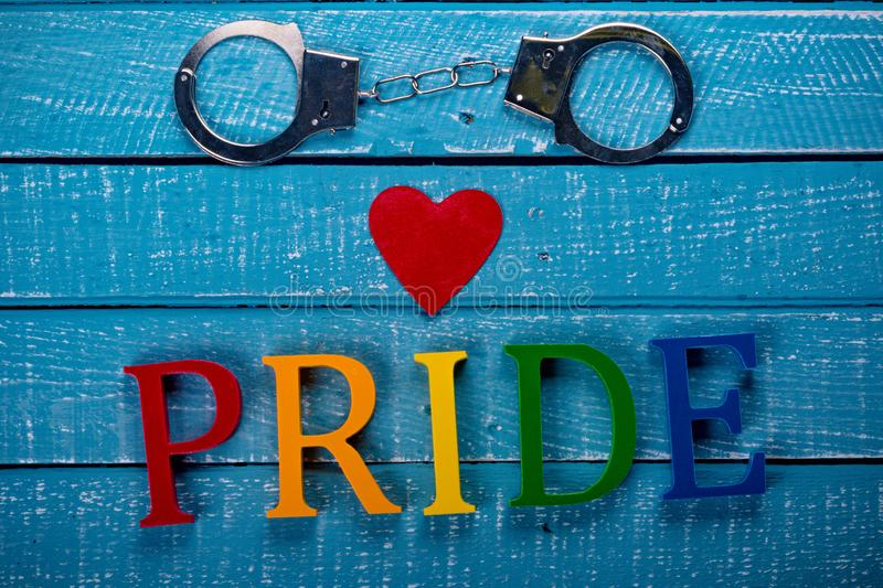 Top down photo of Gay Pride concept. Top down image showing Pride spelt in coloured letters on a blue wooden background with handcuffs and a red heart royalty free stock images