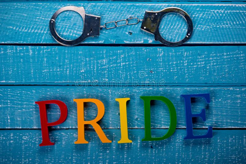 Top down photo of Gay Pride concept. Top down image showing Pride spelt in coloured letters on a blue wooden background with handcuffs royalty free stock image