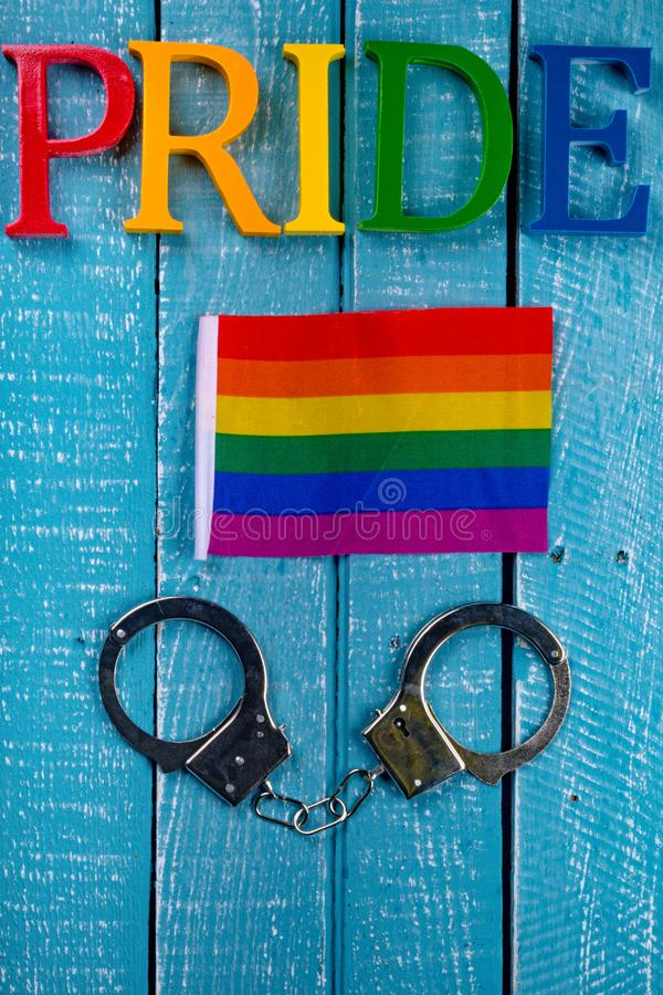Top down photo of Gay Pride concept. Top down image showing Pride spelt in coloured letters on a blue wooden background with a pride flag and handcuffs royalty free stock photo