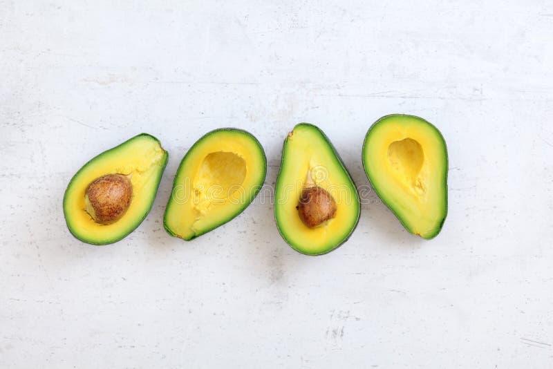 Top down mening, twee die avocado's in de helft, de helften met zaad zichtbaar, op witte steen zoals raad worden gesneden Ruimte  royalty-vrije stock foto's