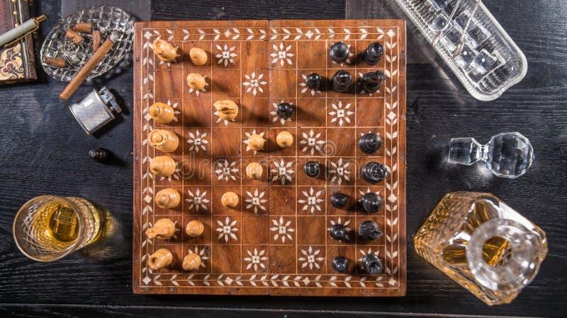 Top down mening van een spel van schaak met een glas whisky stock afbeelding