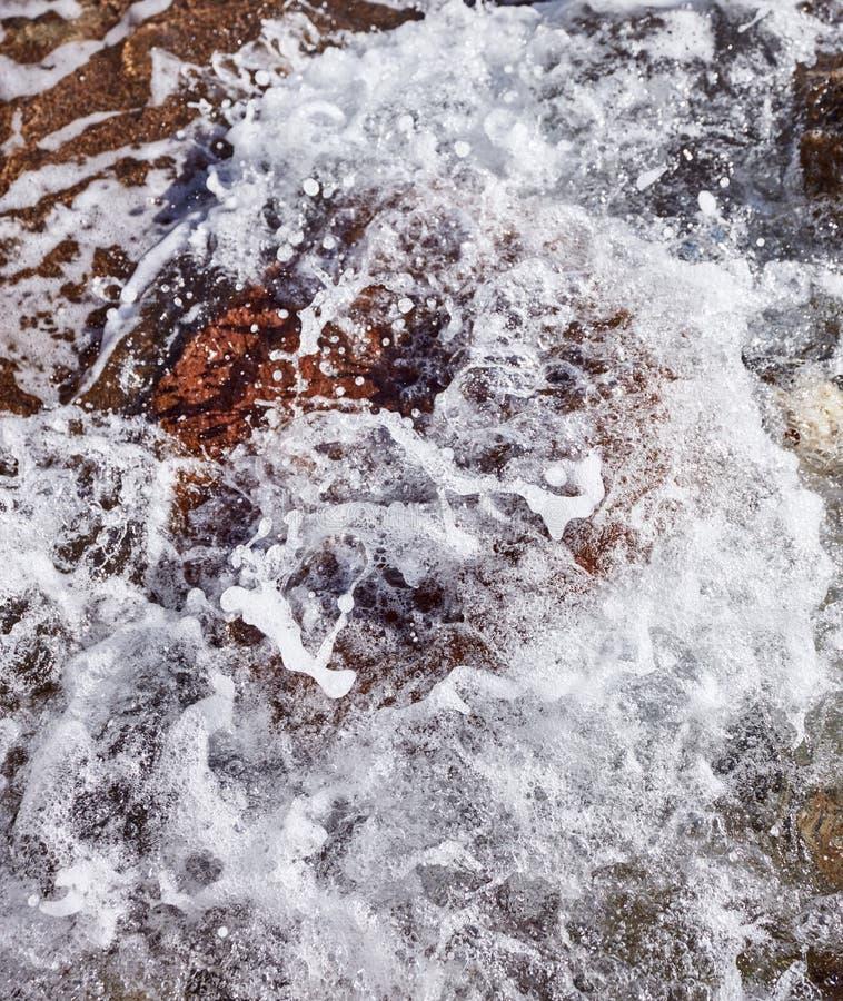 Top down mening van het bespatten van en het verpletteren van overzeese golven aan een rots royalty-vrije stock afbeeldingen