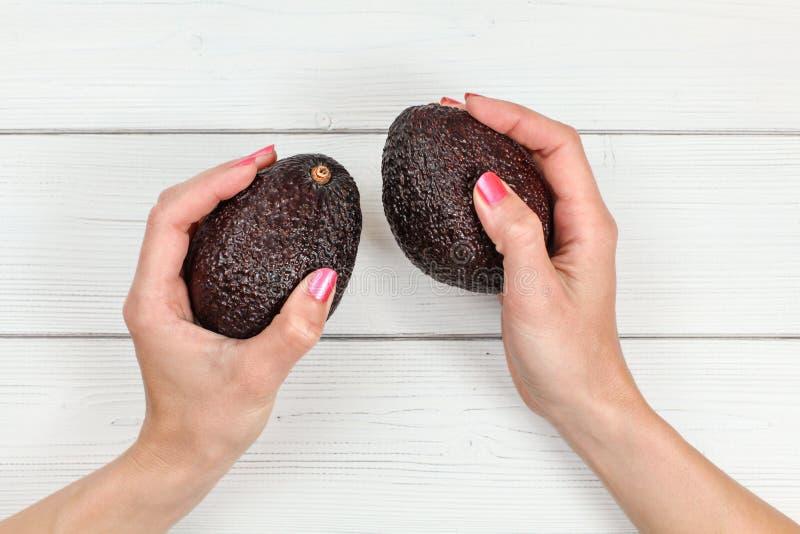 Top down mening, vrouwenhanden met roze spijkers die twee gehele donkere rijpe avocado's over wit raadsbureau houden stock afbeeldingen