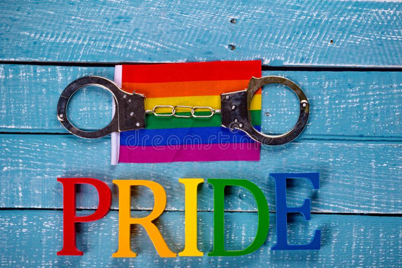 Top down photo of Gay Pride concept. Top down image showing Pride spelt in coloured letters on a blue wooden background with a flag and handcuffs royalty free stock photos